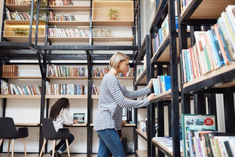 Белокурая молодая симпатичная девушка в striped рубашке и джинсах ища для книги на полке в библиотеке, получая готовый для стоковые фото