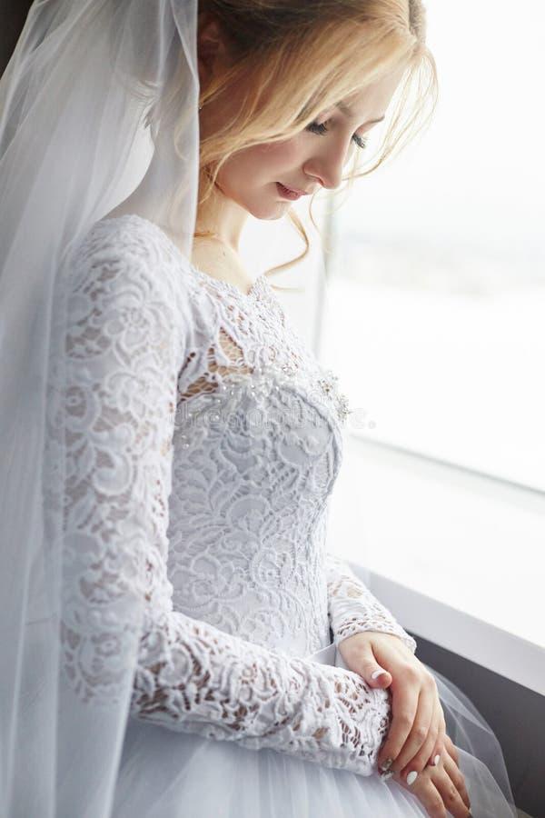 Белокурая невеста в белом платье свадьбы и длинной вуали ждет стоковая фотография rf
