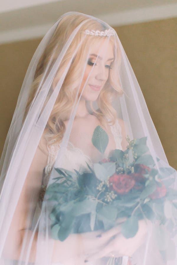 Белокурая невеста с длинной вуалью одела в сексуальном белом нижнем белье стоя на кровати и держа букет свадьбы стоковое фото