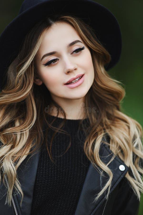 Белокурая счастливая женщина со стильным макияжем в черной кожаной ку стоковая фотография
