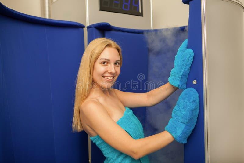 Белокурая с волосами женщина входя в cryotherapy будочку сауны стоковая фотография rf