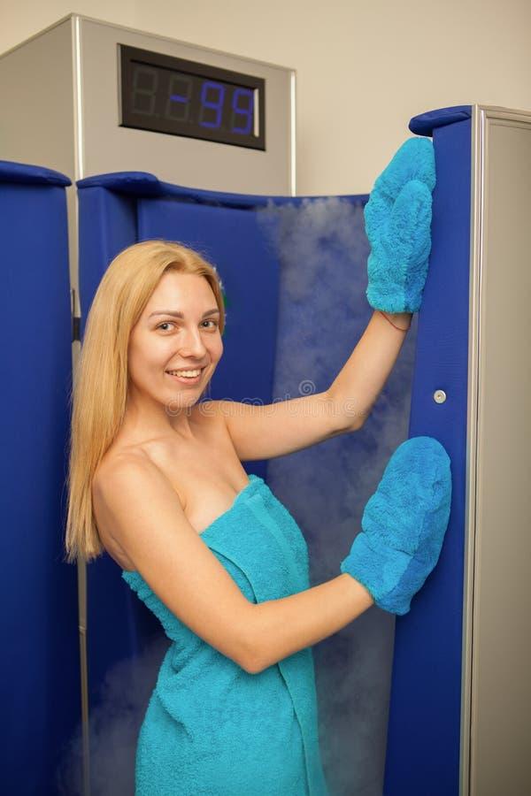 Белокурая с волосами женщина входя в cryotherapy будочку сауны стоковое изображение rf