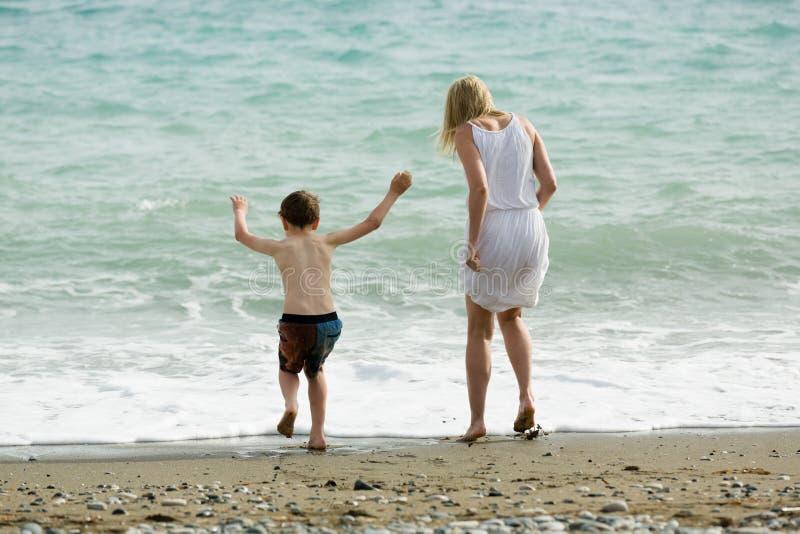 Белокурая тонкая мать и ее ребенок наслаждаются совместно летом, волнами моря на пляже стоковое фото rf