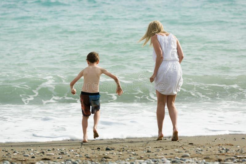Белокурая тонкая мать и ее ребенок наслаждаются совместно летом, волнами моря на пляже стоковое изображение