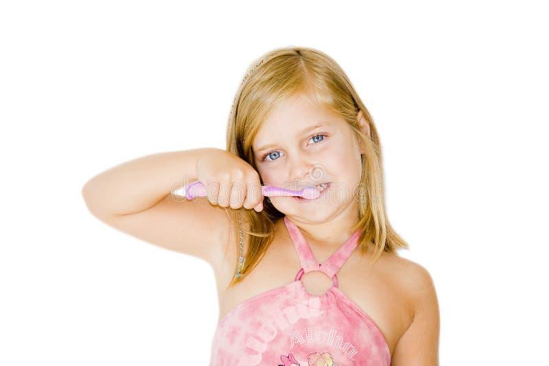 белокурая чистя щеткой девушка ее зубы белые стоковая фотография