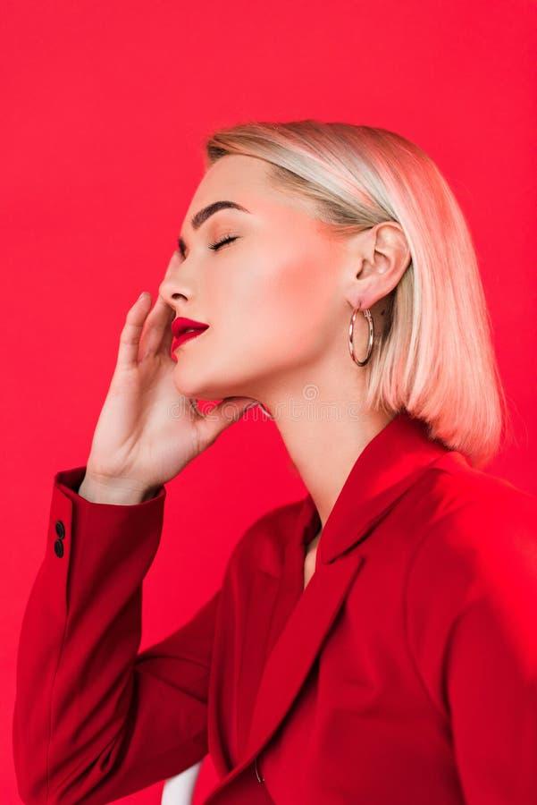 белокурая чувственная девушка представляя в красной куртке стоковое фото