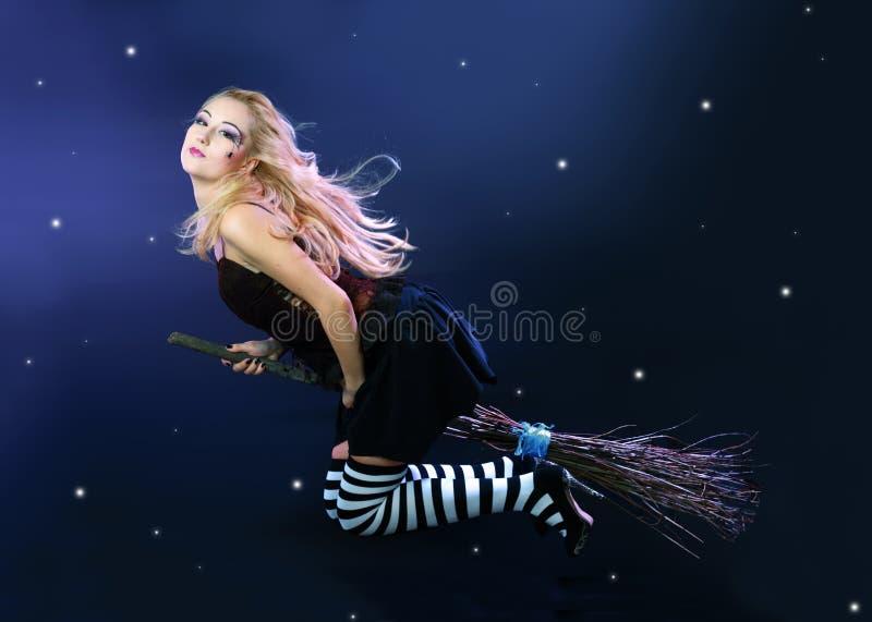 Белокурое летание ведьмы на венике стоковые изображения