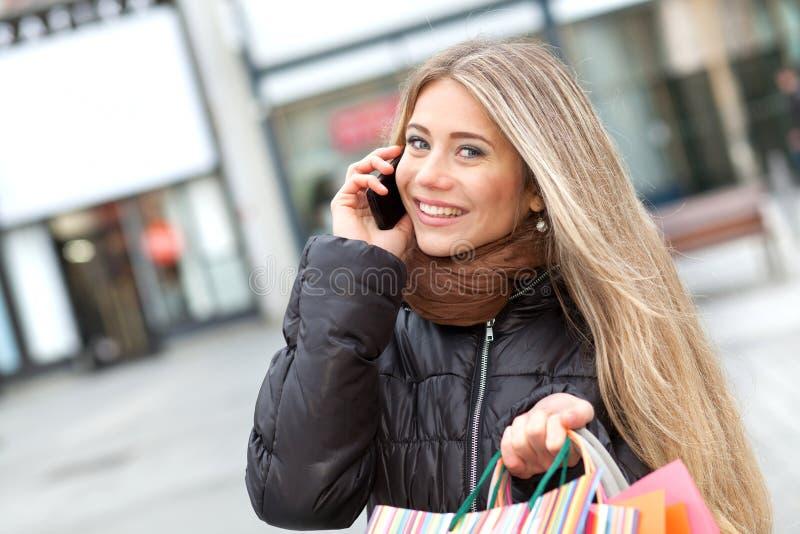 Белокурые покупка и звонить по телефону женщины стоковые фотографии rf