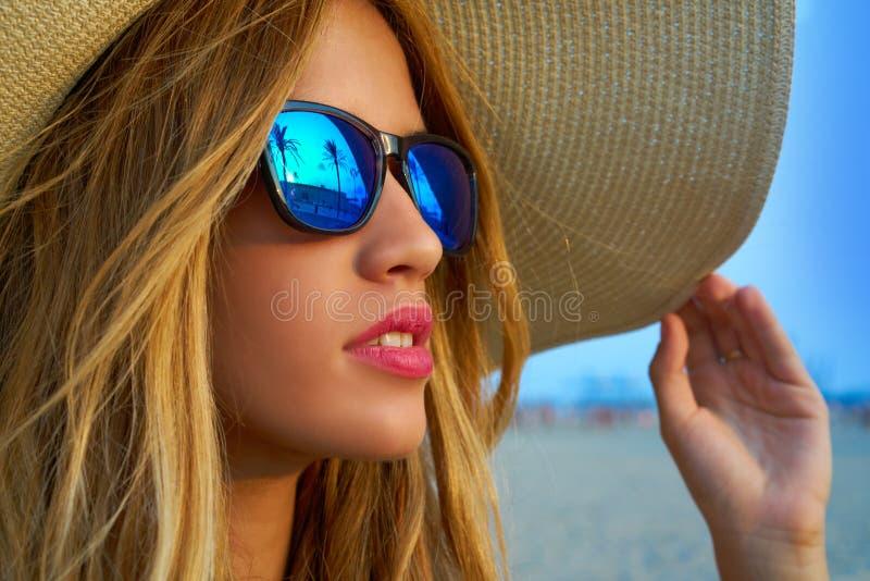 Белокурые предназначенные для подростков солнечные очки и pamela девушки греют на солнце шляпа стоковое изображение