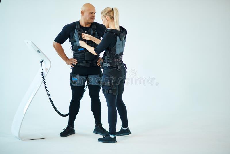 Белокурый женский тренер помогает человеку прикрепить электрод на костюме ems стоковое изображение