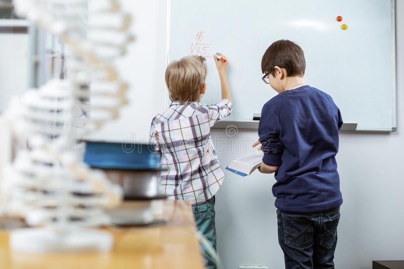 Белокурый маленький студент писать формулы на белом столе стоковая фотография rf