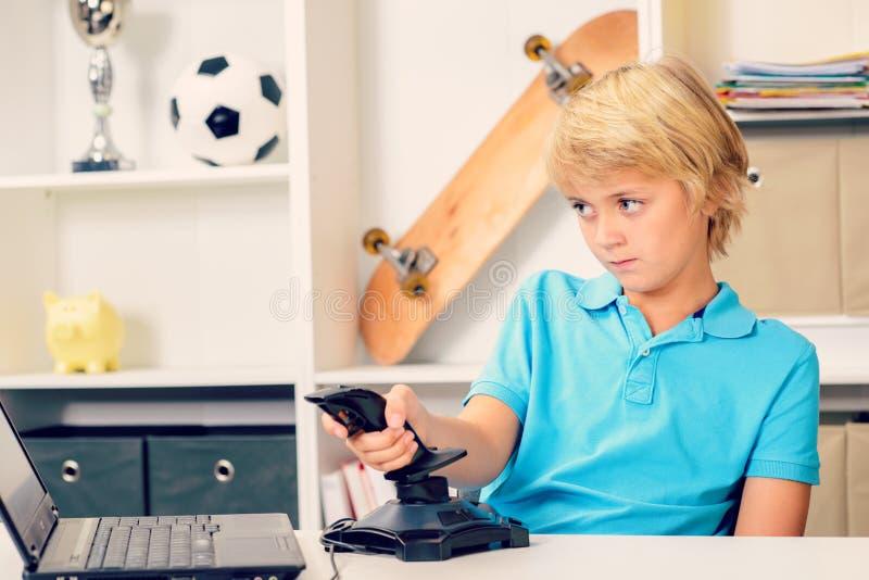 Белокурый мальчик делая домашнюю работу стоковое фото