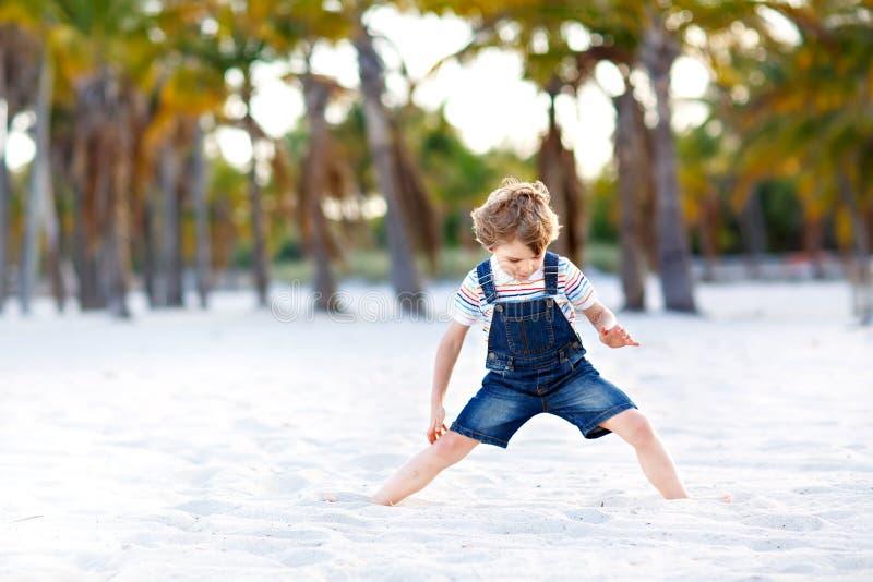 Белокурый мальчик маленького ребенка имея потеху на Miami Beach, Кеы Бисчаыне Счастливый здоровый милый ребенок играя с песком и  стоковое изображение