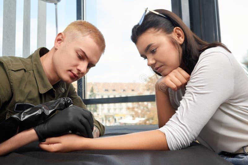 Белокурый мастер в черных перчатках делая татуировку на женской руке стоковые фото
