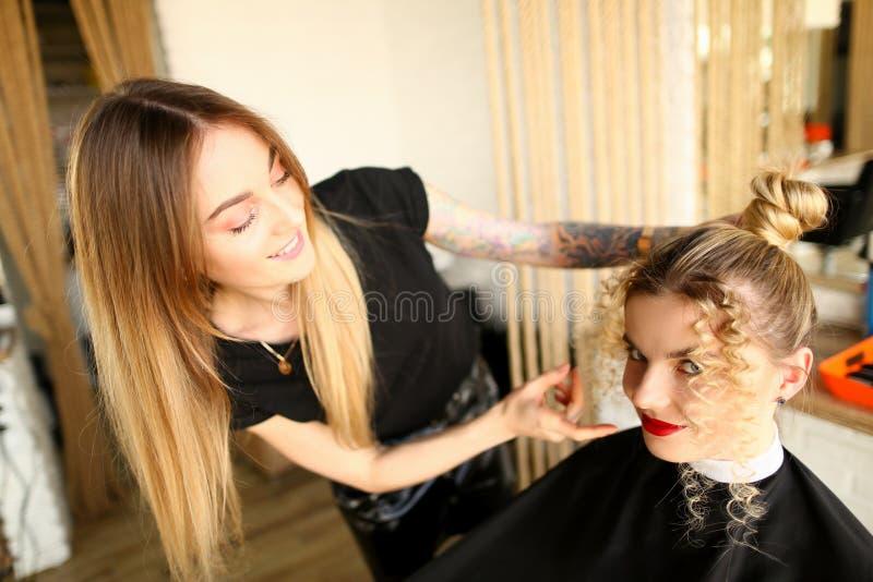 Белокурый парикмахер делая стиль причесок со скручиваемостями стоковые изображения rf