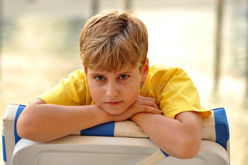 белокурый смотреть камеры мальчика стоковое изображение