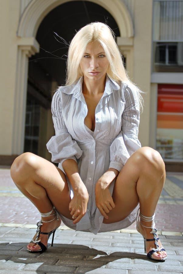 Девушка сидит на корточках в коротких шортах, порно фото теток в маечках