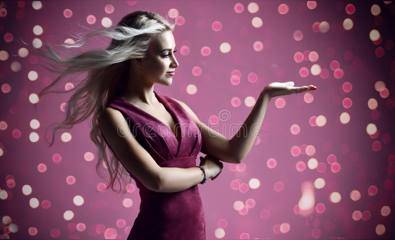 Белокурый cosmetologist beautician женщины указывая рука с космосом текста на пурпурном пинке со светами торжества рождества стоковые фото