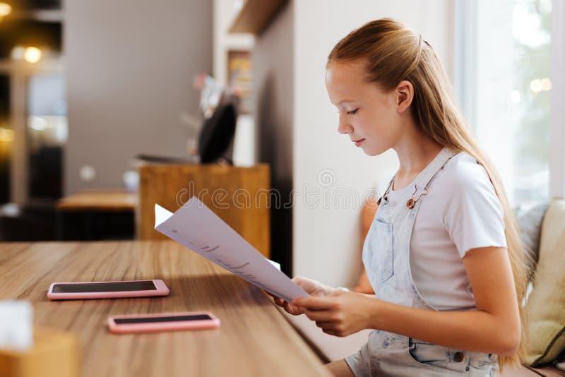 Белокур-с волосами зрачок сидя в кафе с ее друзьями стоковое фото rf