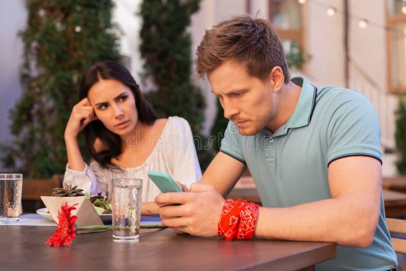 Белокур-с волосами человек чувствуя занятый пока читающ его электронную почту стоковые изображения