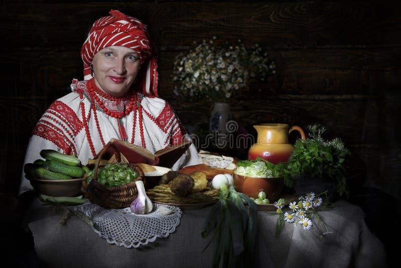 Белорусская женщина на таблице с белорусской едой стоковое фото rf