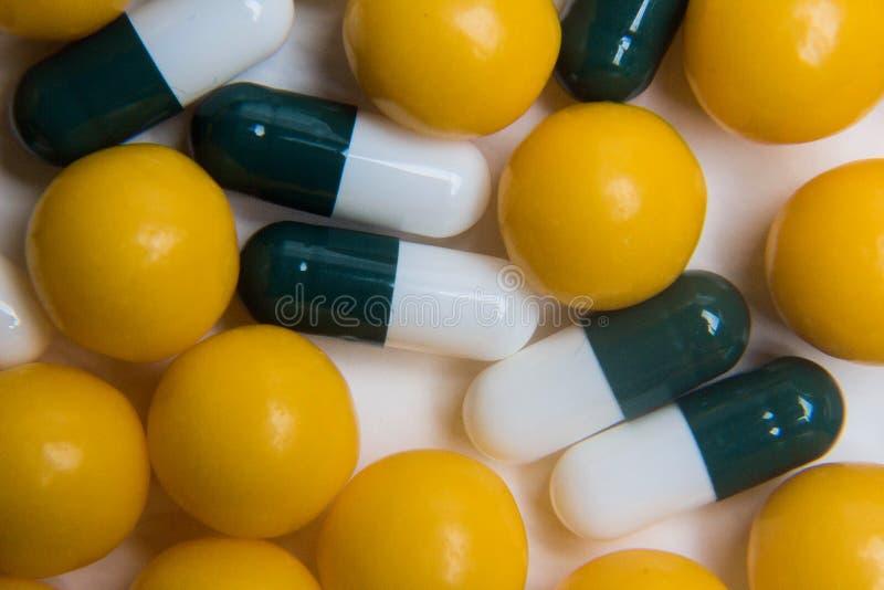 бело-зеленые капсулы таблетки и оранжевый круглый конец-вверх витаминов, медицинская концепция, взгляд сверху стоковое фото rf