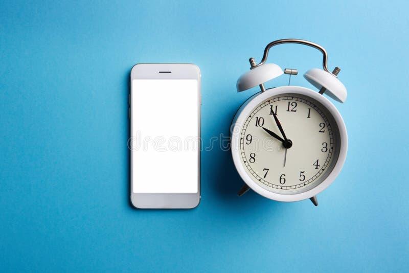 Белые винтажные будильник и мобильный телефон с пустым экраном на пустой голубой предпосылке цвета стоковое изображение