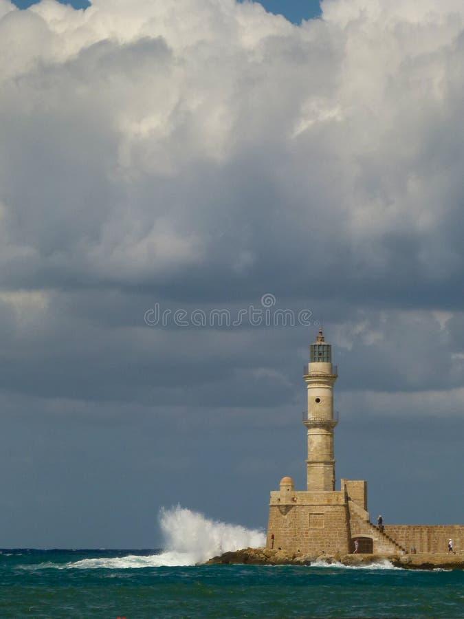 Белые волны с много брызгами бьют на маяке в Chania под хмурым небом стоковые изображения