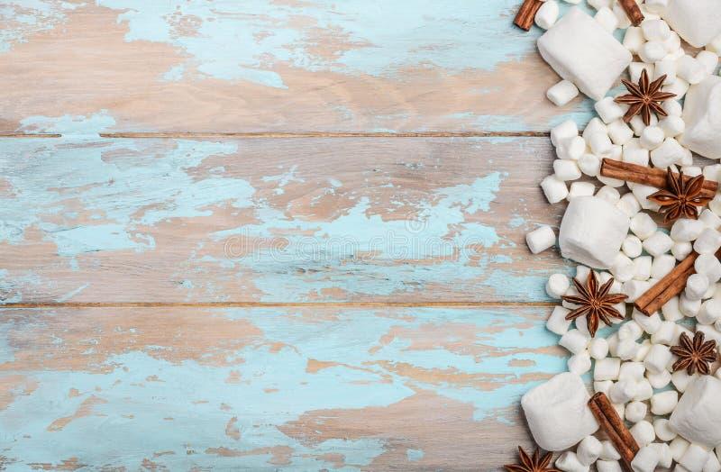Белые зефиры и специи зимы на голубой деревянной предпосылке стоковые изображения