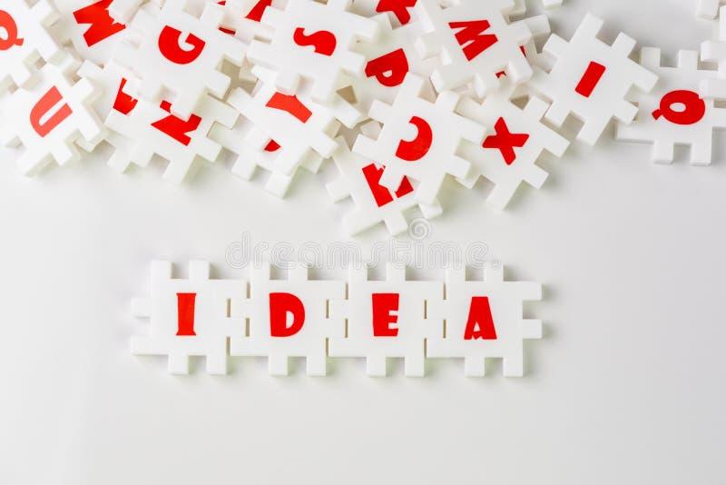 Белые зигзаги головоломки с алфавитами строя слово ИДЕЮ в центре других алфавитов на белой предпосылке, идею дела, стоковая фотография rf