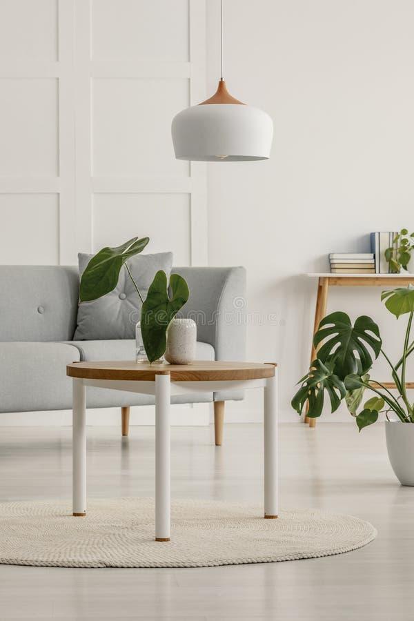 Белые и деревянные лампа и таблица в живя комнате стоковая фотография
