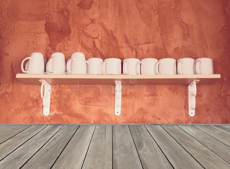 Белые кофейные чашки на деревянной полке с предпосылкой стены цемента grunge, винтажным влиянием фильтра стоковая фотография