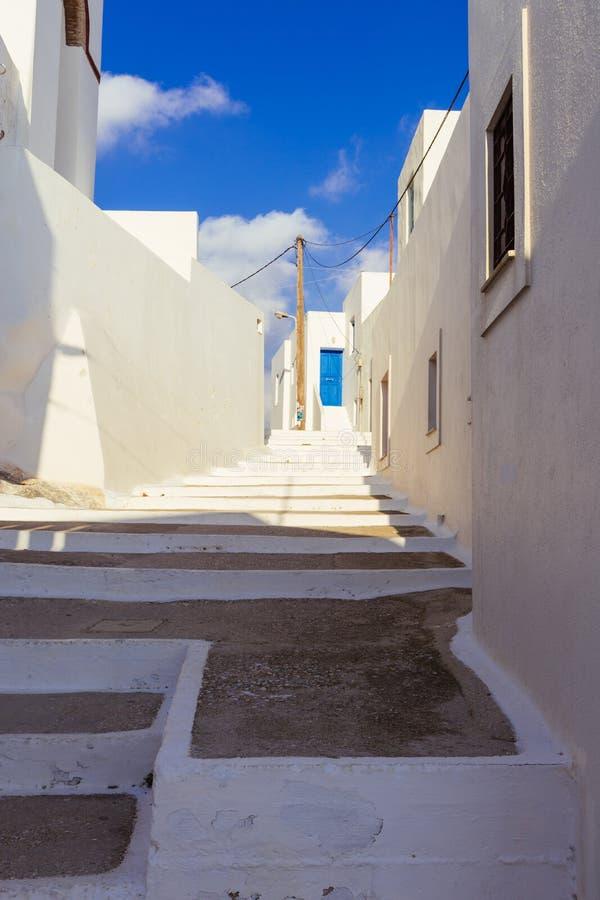 Белые лестницы которые водят к двери ablue в Lagada Amorgos стоковое фото rf