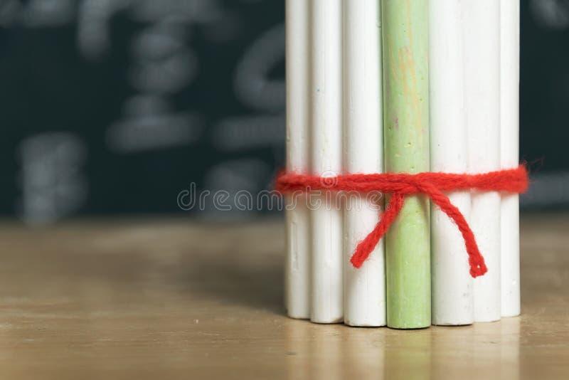 Белые мел связаны вместе с красной пряжей и 1 зеленым мелом стоковое фото rf