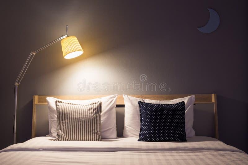 Белые милый интерьер спальни с лампой и деревянный стоковое фото