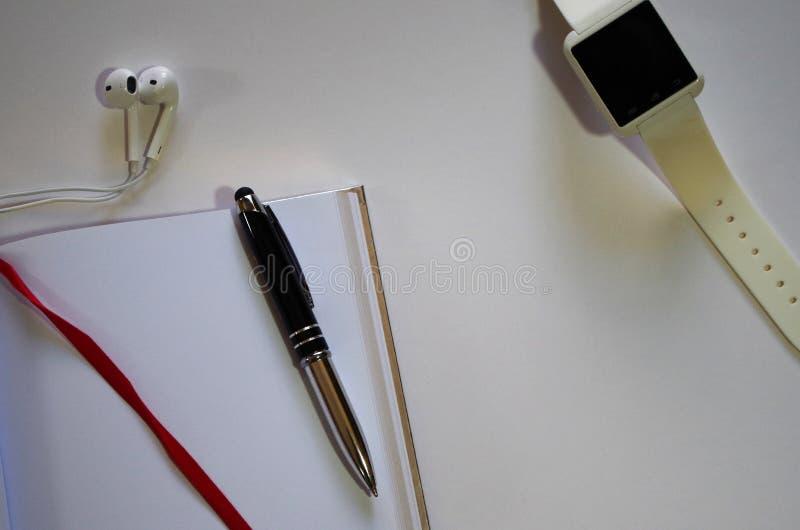 Белые наушники карандаша тетради и взгляд вахты вершин - горизонтальное изображение стоковая фотография