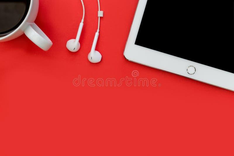 Белые наушники планшета и кофейная чашка на ярком bac красного цвета стоковое изображение rf
