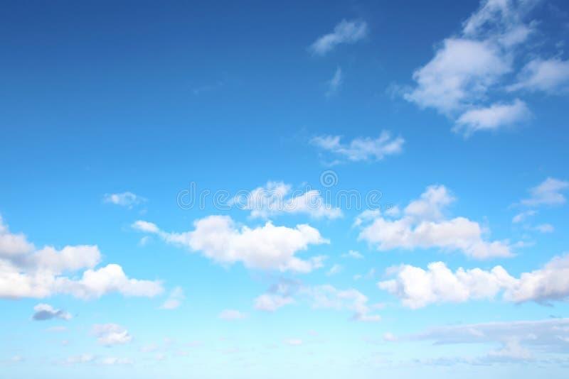 Белые облака различных форм против голубого неба и солнца над поверхностью океана стоковая фотография