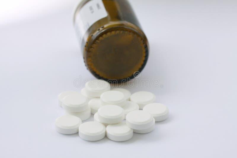 Белые пилюльки разлитые от упаденной бутылки пилюльки Пилюльки и контейнер медицины лежа на белой предпосылке иллюстрируя наркома стоковые фото
