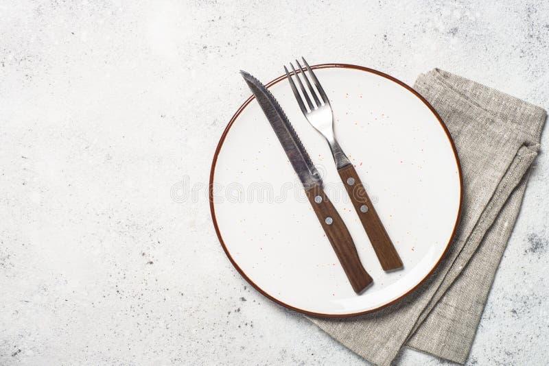 Белые плита, столовый прибор и салфетка ремесла на белой каменной таблице стоковые изображения