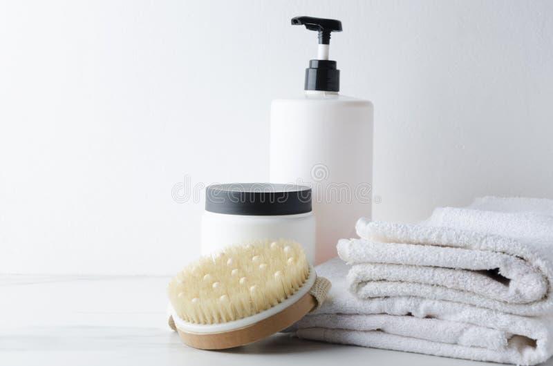 Белые полотенца и бутылки с шампунем, сливк, щеткой тела для процедур спа против белой предпосылки на полке мрамора ванны стоковые изображения rf