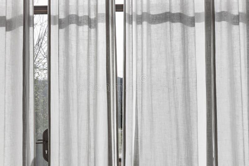 Белые просвечивающие занавесы на большом окне стоковое фото