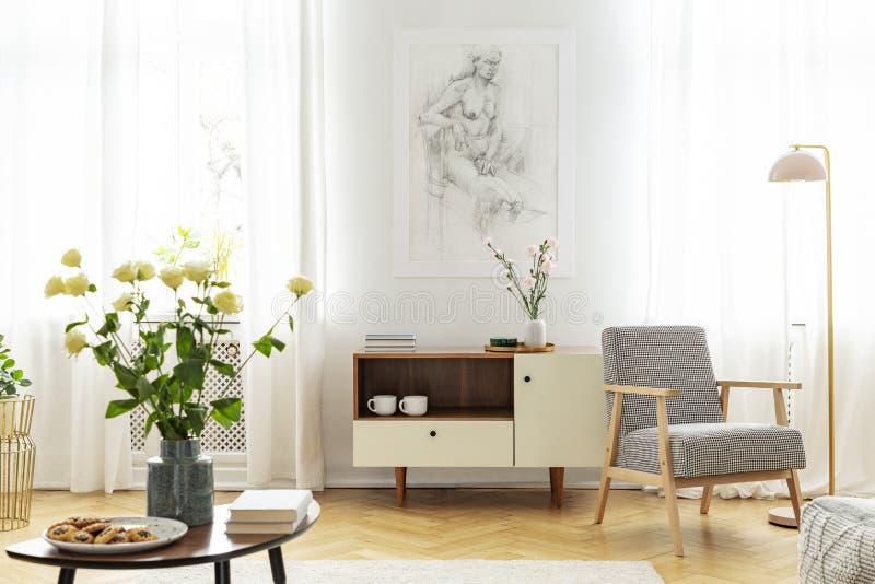 Белые розы в вазе, печеньях на плите и книгах на деревянном журнальном столе в модной живущей комнате с деревянным шкафом и стоковая фотография
