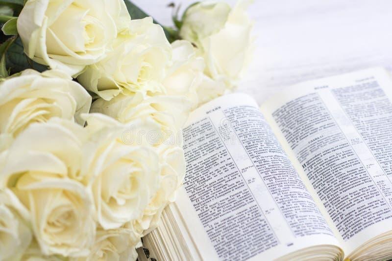 Белые розы и библия на белой деревянной предпосылке стоковые изображения rf