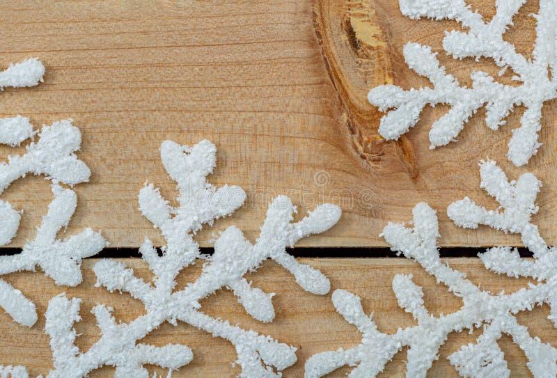 Белые снежинки на светлом деревянном столе Предпосылка украшения рождества и космос экземпляра Счастливые веселое рождество и Нов стоковое изображение