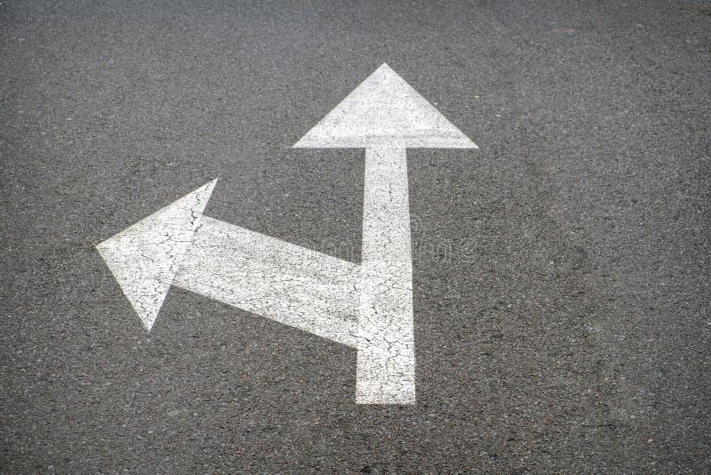 Белые стрелки на дороге асфальта - стрелке улицы стоковое изображение