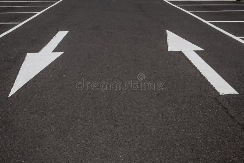 Белые стрелки на черной предпосылке дороги асфальта, стоковое фото rf