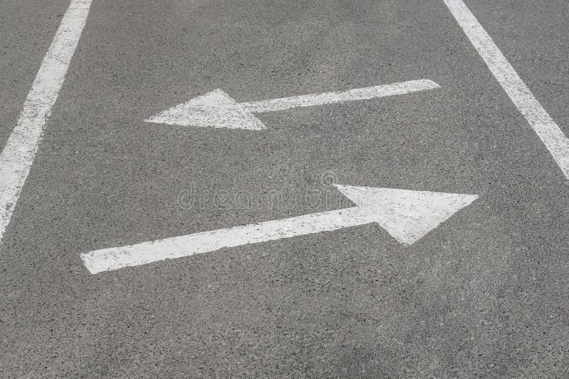 Белые стрелки на черном шоссе асфальта, части дорожной разметки стоковые изображения