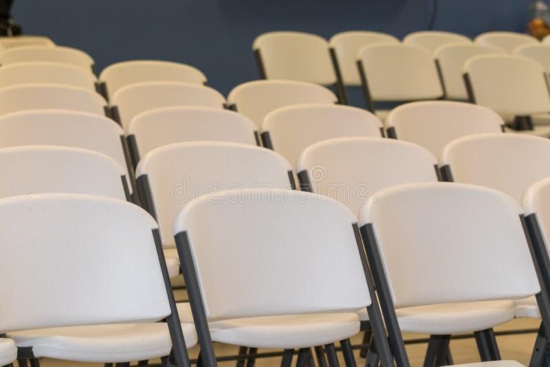 Белые стулья в строках стоковое фото