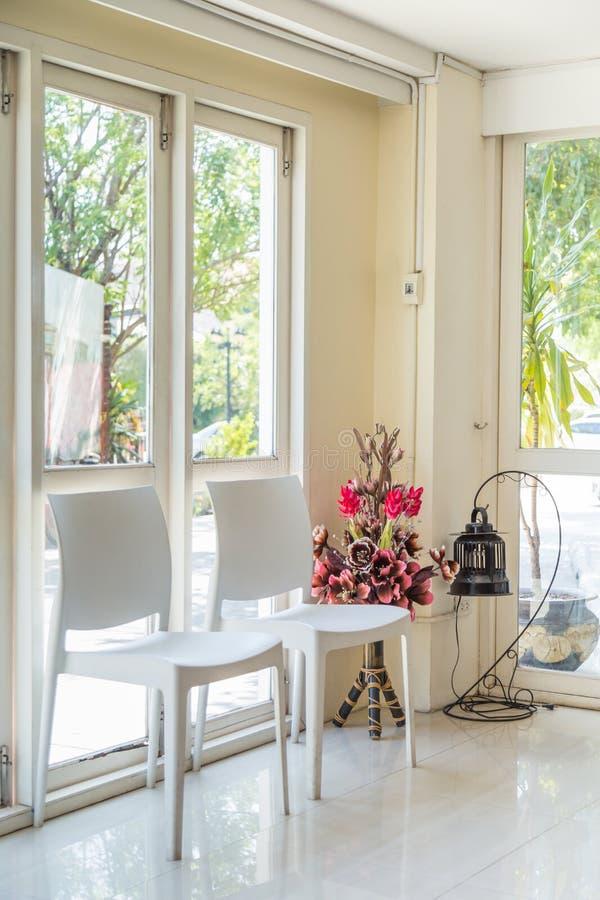 Белые стулья и искусственные цветки с лампой окнами стоковые фото